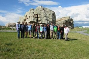 """End of the trip group photo"" at the Big Rock Erratic From Left: Jingxuan Liu, Zuyue Zhang, Maryam Nasizadeh, Alana Semple, Catherine Ross, Joyeeta Bhattacharya, Nancy Zhou, Lacey Pyle, Wey Yi Foo, William Farrell, Christopher Odezulu, Clint Tipette, Yue Yao and Malcolm Ross. Behind the lens: Kevin Root"